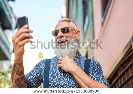Bearded senior using mobile phone outdoor - Hipster mature man having fun with new trends smartphone apps - People lifestyle, technology and social influencer concept  #1350008909