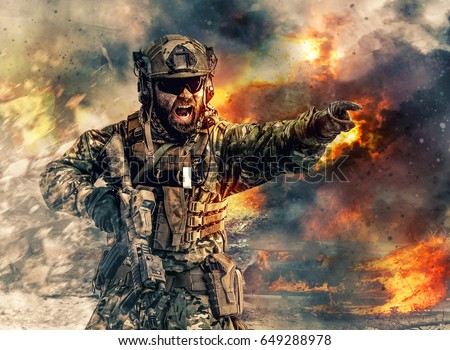 Bearded soldier of special forces in action pointing target and giving attack direction. Burnt ruins, Heavy explosions, gunfire and smoke billowing on background