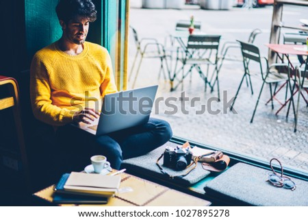 Bearded student typing coursework and searching information in websites on modern laptop device connected to 4G internet.Young man chatting online in social networks at computer sitting in coworking