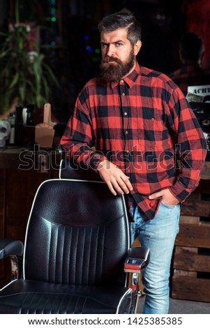 Bearded stylish man. Stylish man at barber shop. Trendy barber shop. Stylish man with beard in plaid shirt standing near vintage barber chair