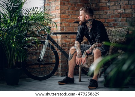bearded tattooed male sitting...