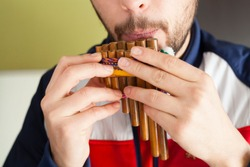 Bearded white male musician blowing a traditional pan flute, wind music, musicology, music education concept.