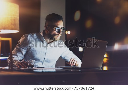 Bearded young businessman working at night office.Man using contemporary mobile laptop.Horizontal.Blurred background. Flares and reflections effect