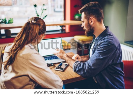 Bearded young man explaining colleague about application on laptop with blank screen area.Two male and female designers discussing creative ideas for developing website working together at netbook