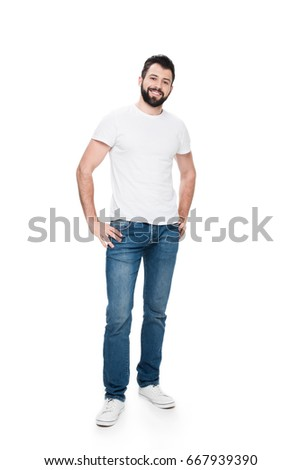 Bearded young man in white t-shirt standing with hands on hips and smiling at camera  #667939390