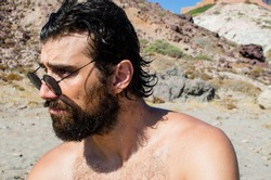 bearded young man with wet hair and sunglasses on the beach