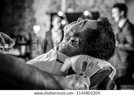 Beards correction in barbershop salon. Black-white photo.
