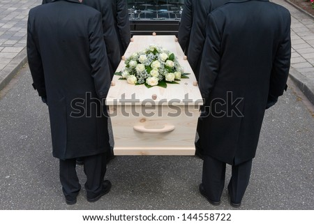 Bearers a carrying a coffin into a car