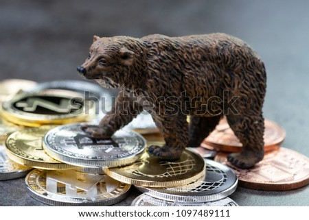 Bearish market concept, price down or falling demand collapse of crypto currency, bear figure standing on various of cryptocurrency physical coins, Bitcoin, Ripple, ZCash, Litecoins, Ethereum.