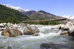 Beas river with wooden bridge in the Kullu valley near Manali.