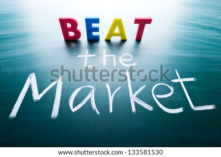 Beat the market, conceptual words on blackboard - stock photo