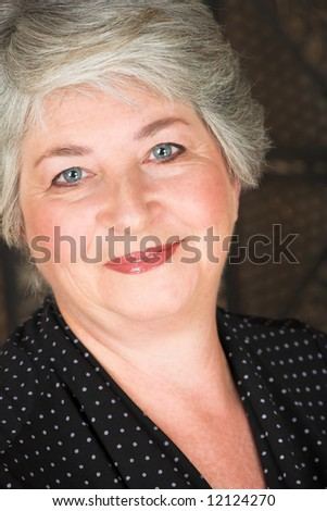 Beatiful older caucasian woman in black blouse, with blue-grey eyes and silver hair. - stock photo