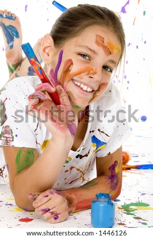 Beatutiful 9 year old girl covered in colorful paints. - stock photo