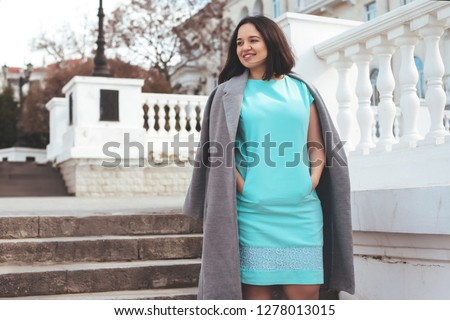 Beauitful plus size model wearing blue dress and grey coat walking outdoor on the city street.