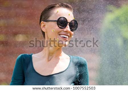 Beauitful  young woman enjoy summer vacation under summer rain
