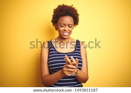 Beauitul african american woman wearing summer t-shirt over isolated yellow background Suffering pain on hands and fingers, arthritis inflammation
