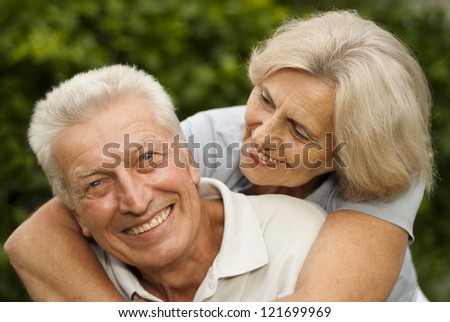 Beauteous elderly couple in the park on a background of green trees and bushes