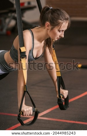 Beautful young woman exercising with TRX straps in gym Photo stock ©