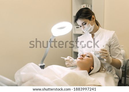 beautician applies cosmetic product to patient woman with brush Foto d'archivio ©