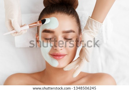 Beautician applying clay face mask on woman face, top view #1348506245