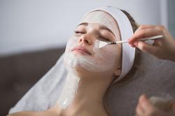 Beautician applying enzymatic peeling on woman's face in spa