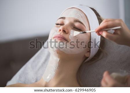 Beautician applying enzymatic peeling on woman's face in spa #629946905