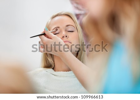Beautician applying eye shadow to young woman at parlor