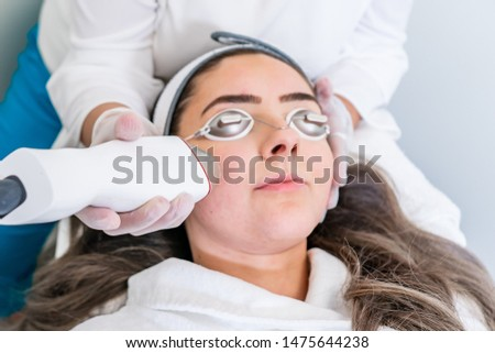 Beautician applying radio frequency microneedling handpiece to a woman's face for skin tightening treatments at a beauty clinic. Stok fotoğraf ©