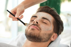 Beautician applying scrub onto young man's face in spa salon