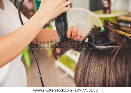 Beautician blow drying woman's hair after giving a new haircut at parlor #1099753133
