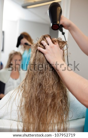 Beautician blow drying woman's hair at parlor