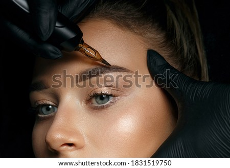 Beautician hand doing brow permanent makeup on an attractive female face Сток-фото ©