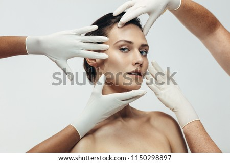 Beautician hands in gloves checking female face skin before aesthetic medical therapy. Woman going under cosmetic treatment on her facial skin.
