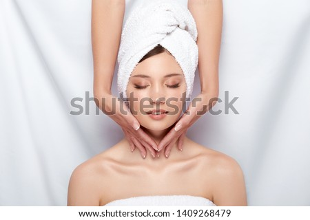 beautician massaging neck of woman in bath towel and with naked shoulders, facial procedures in spa for pretty girl