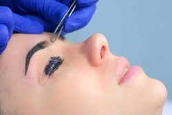 Beautician plucking eyebrows with tweezers to woman in beauty salon during tint eyebrow and lash laminating procedure, side view. Cosmetologist shaping girl's eyebrows in cosmetology clinic.