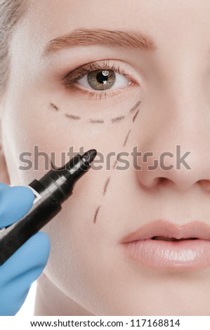 Beautician touch and draw correction lines on woman face. Before plastic surgery operetion. Isolated on white