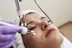 Beautician using electrical impulses for healthy, firm, toned skin. Microcurrent medicine treatment. Beauty young woman