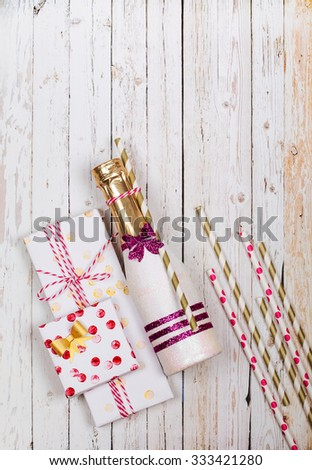 Beautified mini champagne and handmade gifts on a wooden background. View from above