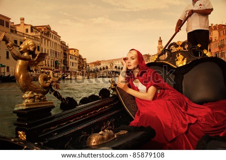 Beautifiul woman in red cloak riding on gandola - stock photo