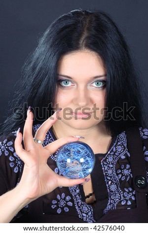 Beautifu smiling black-haired witch holding the magic sphere