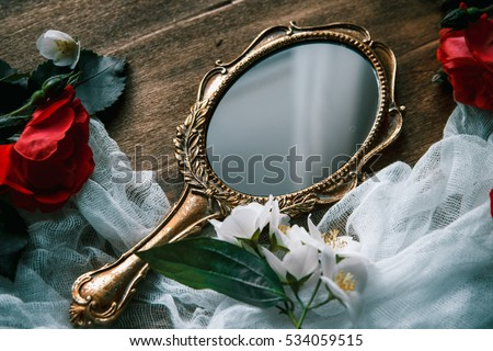 Beautiful a vintage mirror with flowers on wooden background #534059515