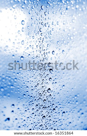 Beautiful abstraction with water drops over deep blue glass background(shallow dof)