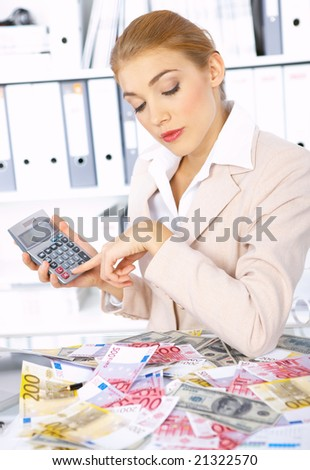 Beautiful accountant using calculator to count cash