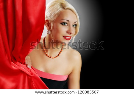Beautiful actress peeks from behind the curtain