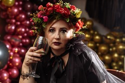 Beautiful adult woman in black halloween costume against the backdrop of balloons and decorations. A witch with black smokey and sparkles on her face