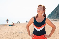 Beautiful adult woman posing on the beach with her hands on her hips. Relaxes after a workout. Sports lifestyle and weight loss concept
