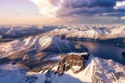 Beautiful aerial landscape view of snow covered mountain and glacier lake with a colorful sunset sky. Taken in Garibaldi, near Squamish and Whistler, North of Vancouver, British Columbia, Canada.
