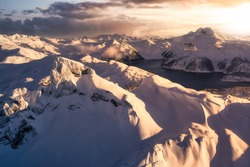 Beautiful aerial landscape view of snow covered mountain, Black Tusk, with a colorful sunset sky. Taken in Garibaldi, near Squamish and Whistler, North of Vancouver, British Columbia, Canada.