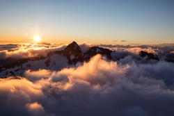 Beautiful aerial landscape view of the rocky mountain peaks covered in glowing clouds during a vibrant sunset. Taken near Squamish and Whistler, North of Vancouver, BC, Canada.