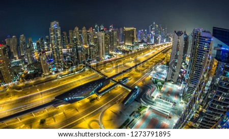Beautiful aerial top view at night  of Dubai Marina  and JLT skyscrapers in Dubai, UAE. Illuminated modern towers with blinking lights and traffic on the road with metro line and tram station. Fishe